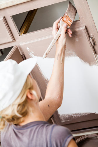 woman painting a kitchen cabinet